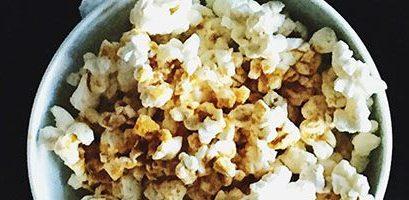 Hand Grabbing Popcorn From Three Tubs